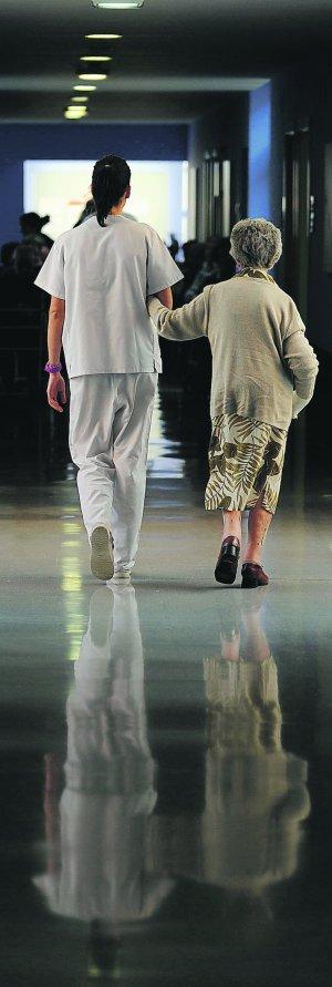 Una trabajadora acompaña a una anciana. :: FERNANDO GÓMEZ/E.C.